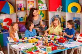 Small students with teacher finger painting in art school class. Mom and kids at home. Children with poster