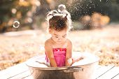 Cute Baby Girl 1-2 Year Old Having Bath With Soap Bubbles Outdoors Close Up. Summer Time. Childhood. poster