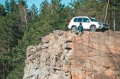 Woman Sitting On Cliff With Beautiful View At Sunny Day. Suv Car At Background. Adventure Concept poster