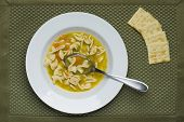 Bowl Of Soup And Crackers. An Overhead View Of A Bowl Of Chicken Noodle Soup And Some Crackers. poster