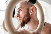 View Through Rings On Male Bearded Athlete With Wireless Headphones Resting And Holding Gymnastics R poster