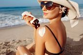 Beautiful Woman In Bikini Applying Sun Cream On Tanned  Shoulder. Sun Protection. Skin And Body Care poster