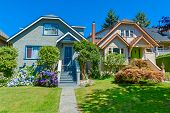 Snug Warm Family Houses Side By Side. Residential House With The Pathway Over Front Yard Lawn On Blu poster