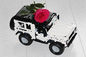 The Toy Car Suv Carries A Real Red Rose. The Car Is Made Of Designer, It Is Black And White. Flower  poster