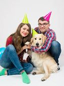 Young Smilling Family With Their Dog Golden Retriever Celebrate One Year Birthday. Friendship. Love. poster