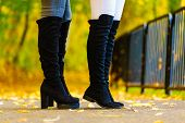 Two Unrecognizable Women Wearing Long Black Heeled Knee High Boots And Jeans. Autumn Fashion, Warm F poster