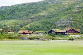 Norwegian Country House. Scenic Summer View Of Cottage Houses In Mountain Village, Norway. House Wit poster