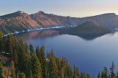 foto of pacific rim  - Landscape at sunrise of Crater Lake National Park with conifers Wizard Island and crater rim Oregon USA - JPG