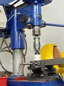 Stationary drilling machine with attached metal hole cutting piece