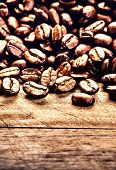 Roasted Coffee Beans On Grunge Wooden Background Closeup. Fresh Coffee Beans On Vintage Table Ready