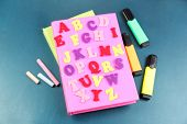 English alphabet, books and markers on school desk