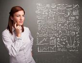 foto of anal  - Pretty young woman looking at stock market graphs and symbols - JPG
