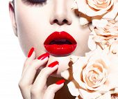 Fashion Sexy Woman with flowers. Vogue style Model girl face with roses. Red Sexy Lips and Nails clo