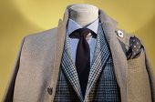 pic of coat tie  - Close up of a mannequin in beige coat checkered Jacket striped shirt and dark blue tie - JPG