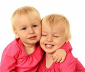 Cute two year old identical twin girls hugging.