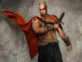 stock photo of legion  - Wounded gladiator with  sword covered in blood isolated on grey - JPG
