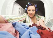 stock photo of tramp  - a woman reaching in the dryer for clothes - JPG