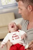 picture of daddy  - Closeup photo of father holding crying baby - JPG