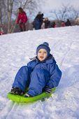 foto of snow-slide  - young boy on sledge sliding down on snow - JPG