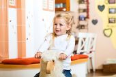 Girl rocking and playing with rocker horse in living room