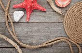 Sea travel frame decor with seashells and rope over wooden background