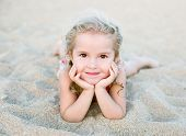 picture of children beach  - Happy little girl lying on the sand on the beach - JPG