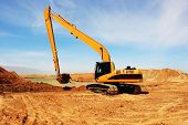 foto of oversize load  - Orange excavator  at Construction irrigation canal in Desert  - JPG