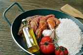 image of negro  - ingredients to prepare a spanish paella or arroz negro on a rustic wooden table - JPG
