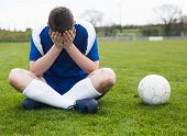 stock photo of disappointment  - Disappointed football player in blue sitting on pitch after losing on a clear day - JPG