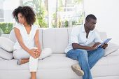 picture of not talking  - Attractive couple not talking on the couch at home in the living room - JPG