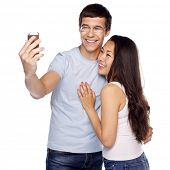 picture of two women taking cell phone  - Young smiling interracial couple taking selfie on mobile phone isolated on white background - JPG
