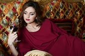 foto of night gown  - Sensual woman with a red wine glass on a magnificent sofa - JPG