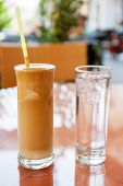 image of frappe  - Frappe served with a glass of water on cafe table. Crete Greece