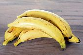 stock photo of plantain  - sweet ripe plantain bananas on rustic table - JPG