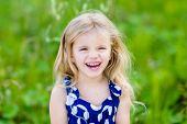 foto of laugh  - Pretty laughing little girl with long blond curly hair outdoor portrait in summer park on bright sunny day - JPG