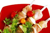 picture of greenery  - raw  chicken kebabs served with cherry and greenery - JPG