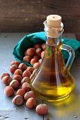stock photo of hazelnut  - Hazelnut oil in a glass bottle and unpeeled nuts on the table - JPG