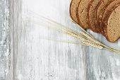 image of fresh slice bread  - slices of rye bread and ears of corn wheat on a light wooden background.health and diet food. copy space background ** Note: Shallow depth of field - JPG