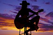 pic of redneck  - a silhouette of a woman sitting on her stool holding on to her guitar - JPG