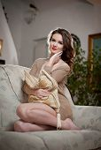 stock photo of tight dress  - Young sensual woman sitting on sofa relaxing - JPG
