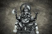 picture of camphor  - idol of Hindu god Ganesha on cracked stone wall background - JPG