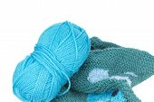 stock photo of knitting  - Blue knitting yarn and knitted piece of patterned sweater isolated on the white background - JPG