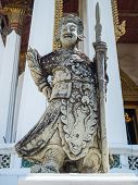 picture of rock carving  - Chinese standing giant carved out of rock in Wat Suthat Thep Wararam Bangkok Thailand - JPG