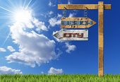 stock photo of directional  - Wooden directional sign with two arrows in opposite direction with text beach and city hanging with metal chain a wooden pole on blue sky with clouds sun rays and green grass - JPG