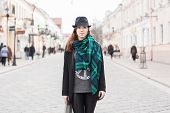 foto of cloak  - Portrait of a beautiful girl in a black cloak with a scarf standing on the square - JPG