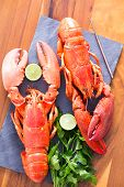 picture of lobster tail  - Close up Appetizing Ready to Eat Cooked Lobsters Duo on a Cutting Board with Lime and Parsley Served on a Wooden Table - JPG