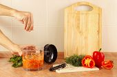 foto of blender  - Hands of chef salt cooked vegetable salsa in a blender - JPG