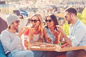 stock photo of alcoholic drinks  - Four young happy people eating pizza and drinking beer while sitting at the bean bags on the roof of the building - JPG