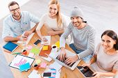 pic of casual wear  - Top view of group of business people in smart casual wear working together and smiling while sitting at the wooden desk - JPG