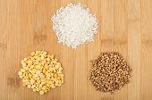 picture of buckwheat  - Three heap of dry rice buckwheat and peas on bamboo board - JPG